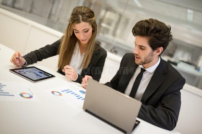 工作在桌附近的商人在现代办公室 免版税库存图片