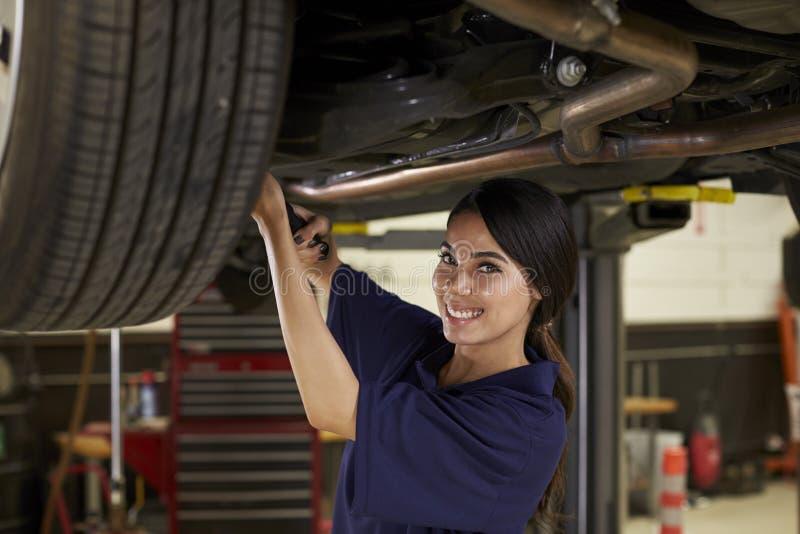 工作在汽车下的女性汽车机械师画象  免版税图库摄影
