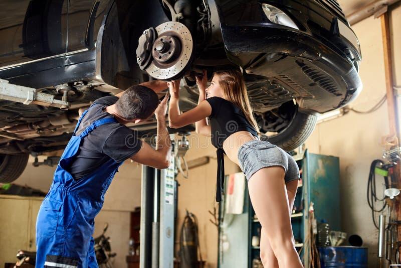 工作在汽车服务的男人和妇女 库存图片