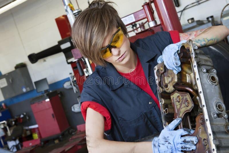 工作在汽车机器零件的年轻女性技工在车间 免版税库存照片