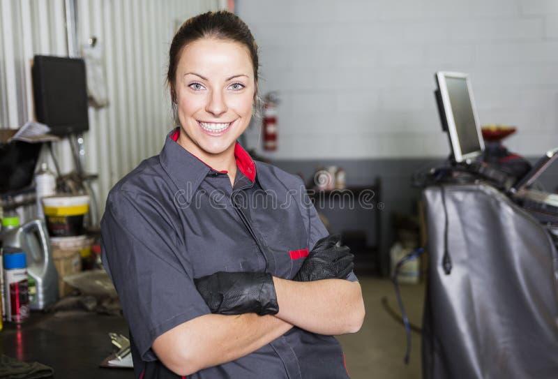 工作在汽车的技工妇女在他的商店 库存图片