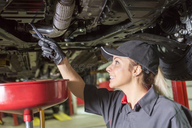 工作在汽车的技工妇女在他的商店 库存照片