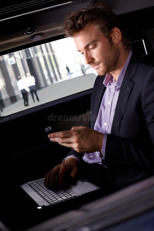 工作在汽车的精明的商人 图库摄影