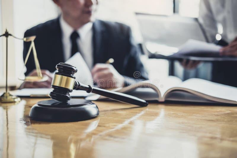 工作在法庭的男性律师或顾问开与客户的会谈是与不动产,法律合同纸的咨询  库存图片