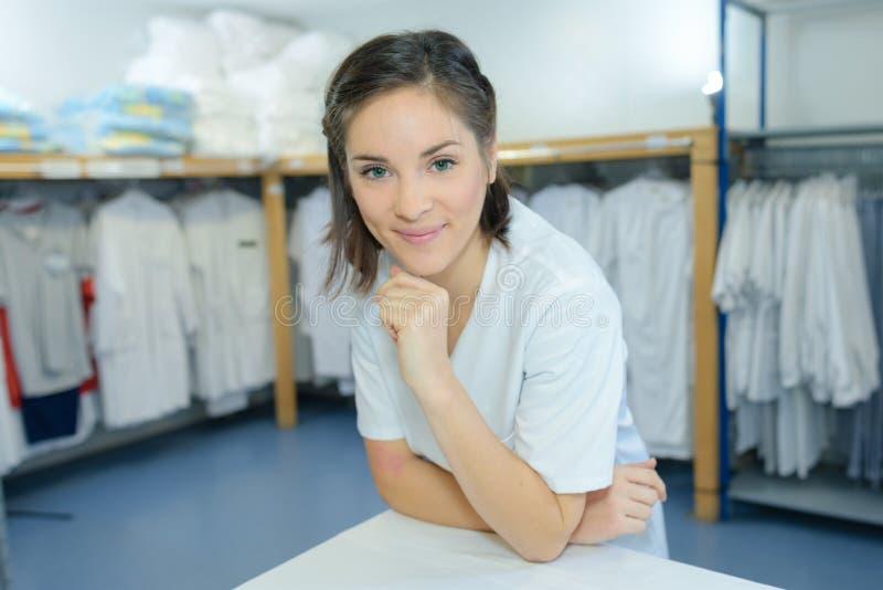 工作在洗衣店的美丽的年轻女人 图库摄影