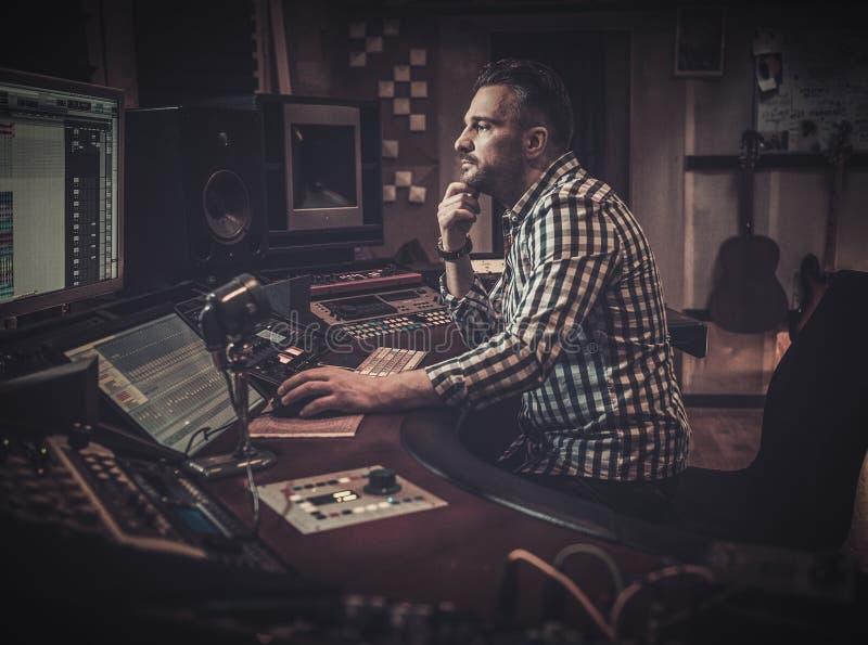 工作在混合的盘区的录音师在精品店录音室 图库摄影