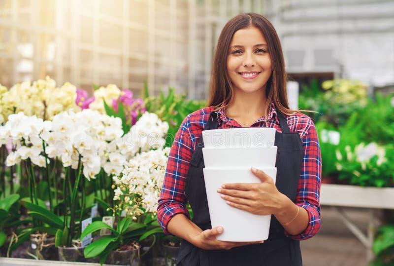 工作在温室里的愉快的年轻卖花人 图库摄影