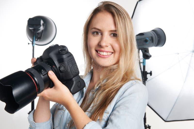 工作在演播室的女性专业摄影师 库存图片