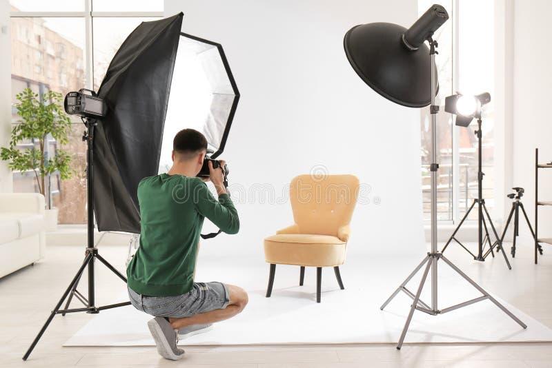 工作在演播室的年轻摄影师 免版税库存图片
