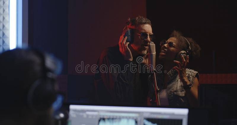 工作在演播室的歌手和录音师 免版税库存图片