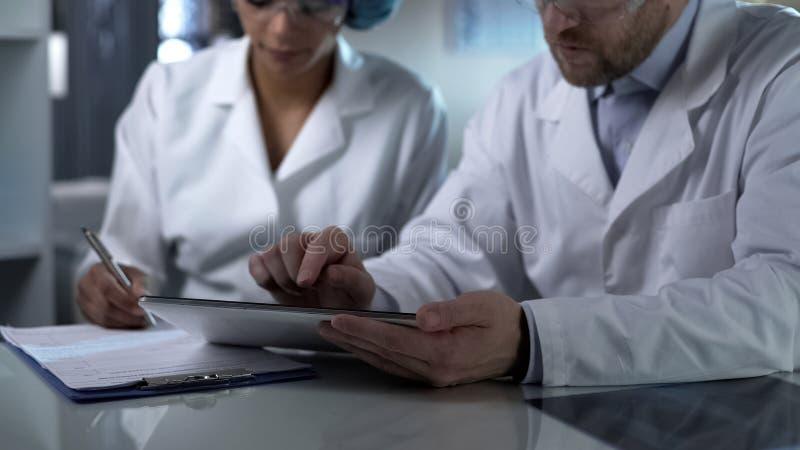 工作在片剂和女性助理的科学家做笔记,诊所配合 免版税库存图片