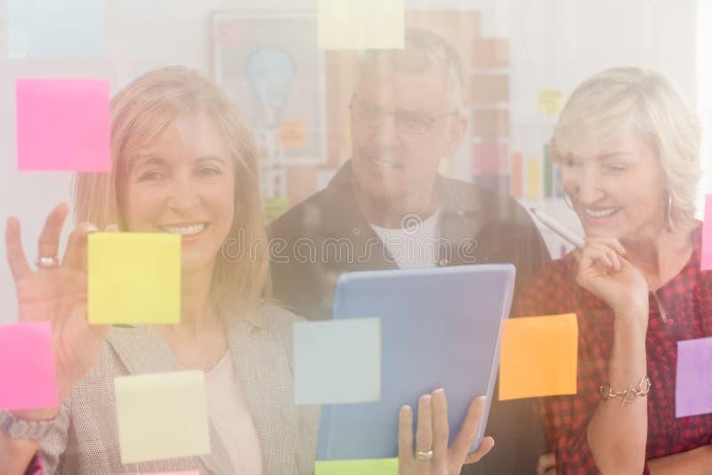 工作在片剂的微笑的企业队 免版税库存图片