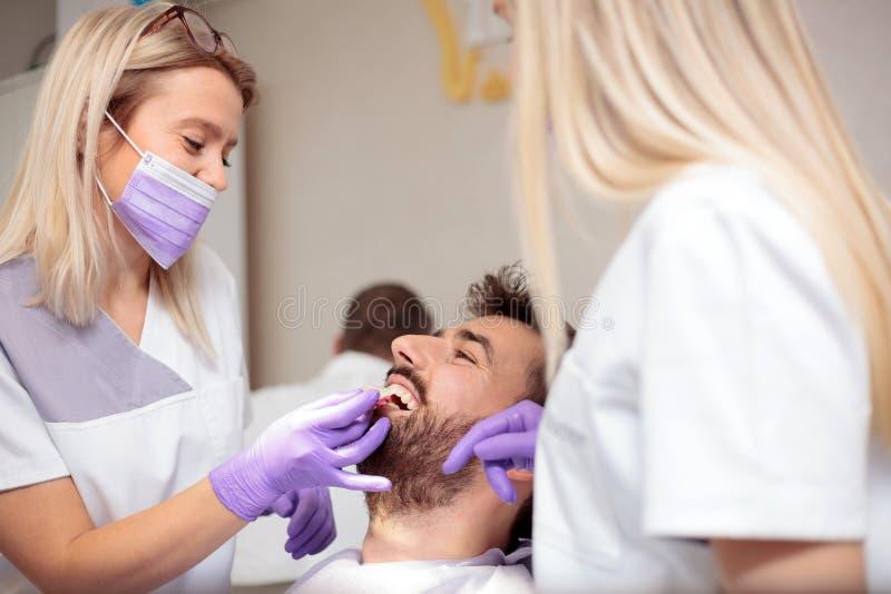 工作在牙齿诊所的两位年轻女性牙医 漂白男性耐心牙和使用口气图对马赫颜色 免版税库存图片