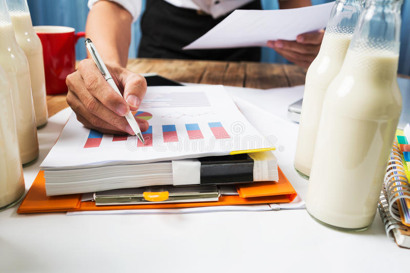 工作在牛奶瓶质量管理重活骗局的商人 库存照片