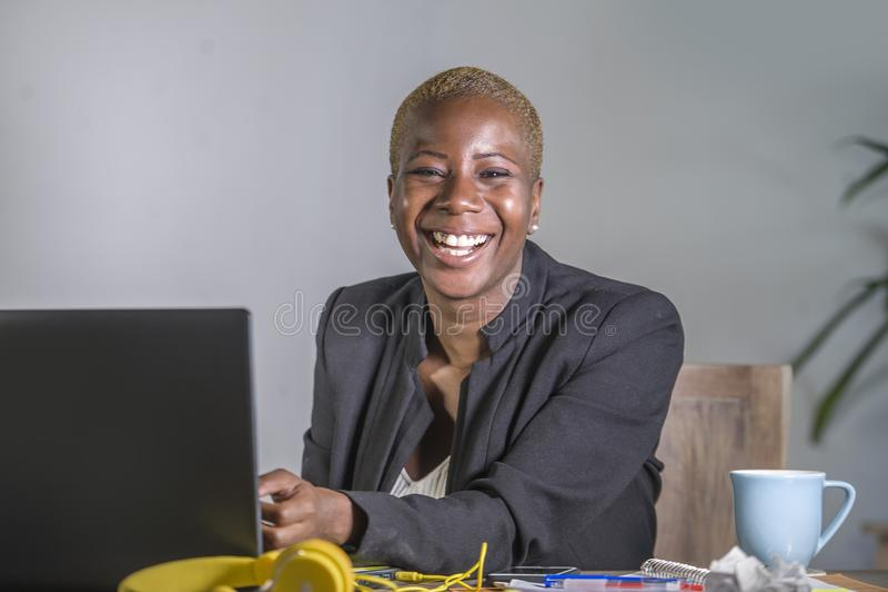 工作在现代办公室微笑的快乐的havi的年轻愉快和成功的黑人美国黑人的女商人公司画象  免版税图库摄影