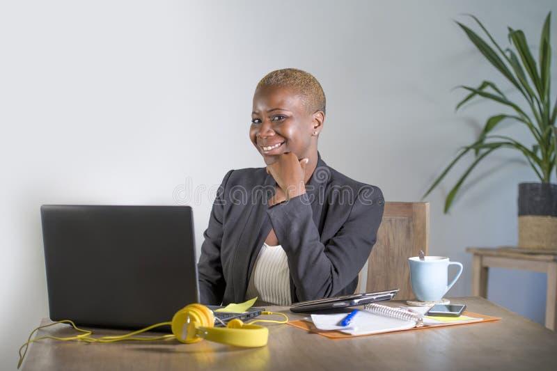 工作在现代办公室微笑的快乐的havi的年轻愉快和成功的黑人美国黑人的女商人公司画象  免版税库存图片