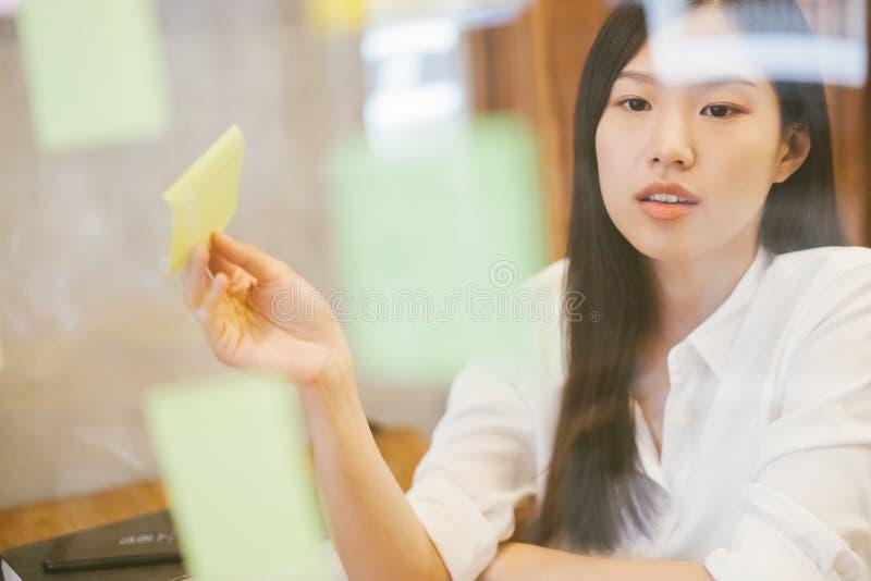 工作在现代办公室的年轻创造性的亚裔妇女 见面的用途柱子 库存图片
