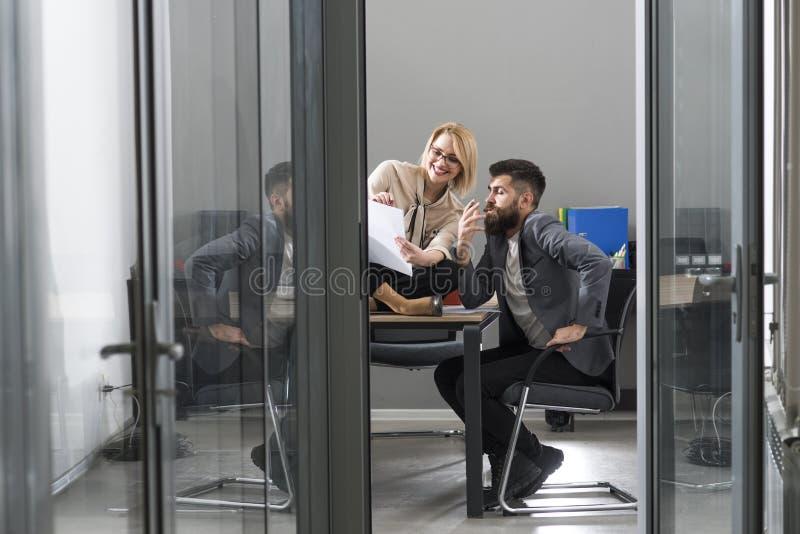 工作在现代办公室的年轻同事愉快的夫妇  两个工友谈论工作,运作与文件 免版税库存照片