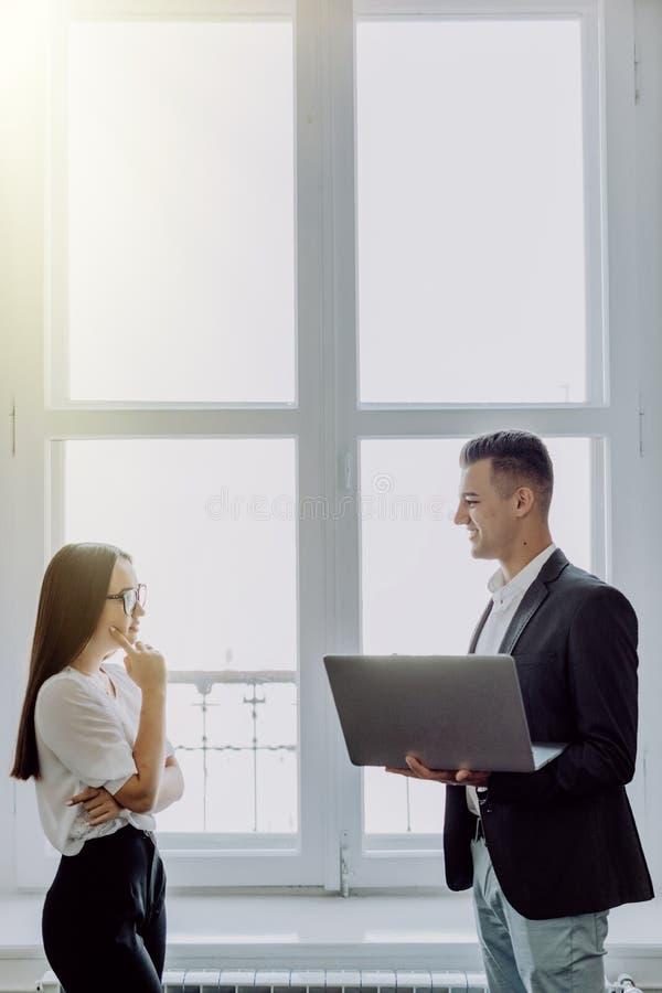 工作在现代办公室的年轻商务伙伴愉快的夫妇  研究膝上型计算机的两个工友,当站立在窗口,拷贝附近时 免版税库存照片