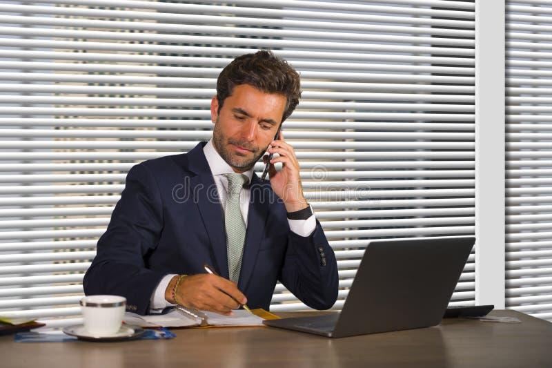 工作在现代办公室的年轻愉快和繁忙的商人生活方式公司公司画象谈话在手机由风 库存图片