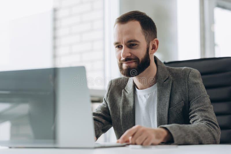 工作在现代办公室的有胡子的年轻商人 人佩带的白色衬衫和制造笔记关于本文 全景窗口 库存图片