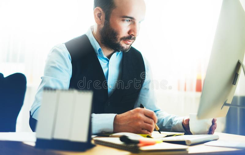 工作在现代办公室的有胡子的年轻商人 顾问人想法的看在显示器计算机 键入在keyboar的经理 库存照片