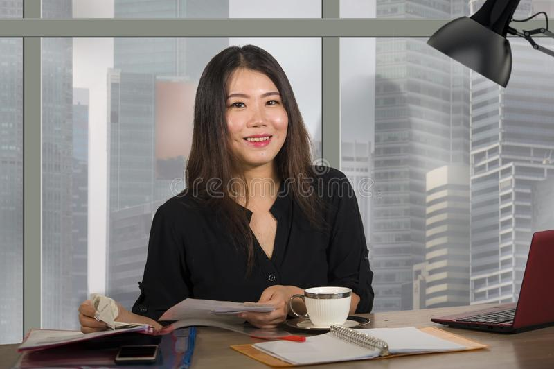 工作在现代办公计算机书桌的年轻愉快和美丽的亚裔韩国企业家妇女在c的中心商务区 图库摄影