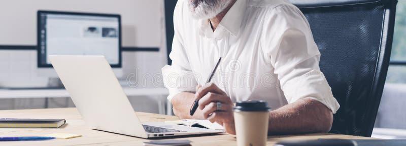 工作在现代coworking的办公室的沉思商人 使用当代流动膝上型计算机的确信的人 宽 播种 库存图片