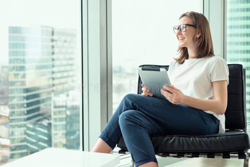 工作在现代办公室的微笑的女商人 免版税库存图片