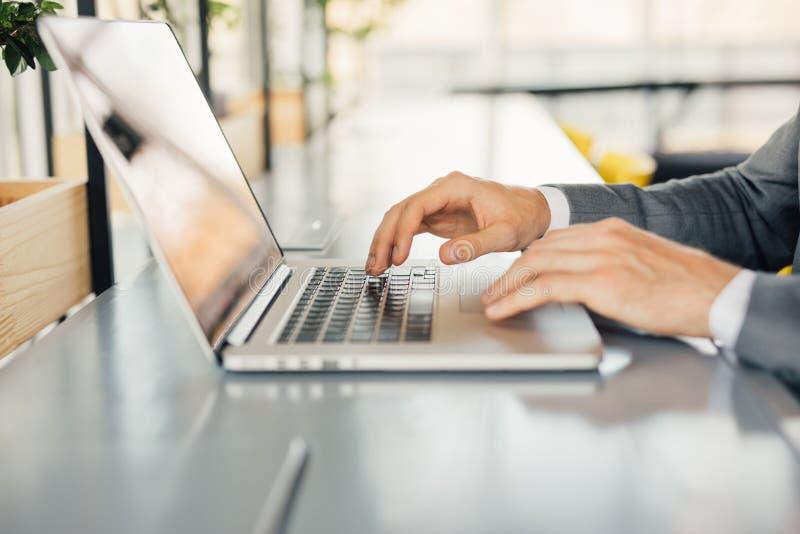 工作在现代顶楼办公室的照片商人 供以人员坐的木桌和使用当代笔记本,发短信给消息键盘 免版税图库摄影