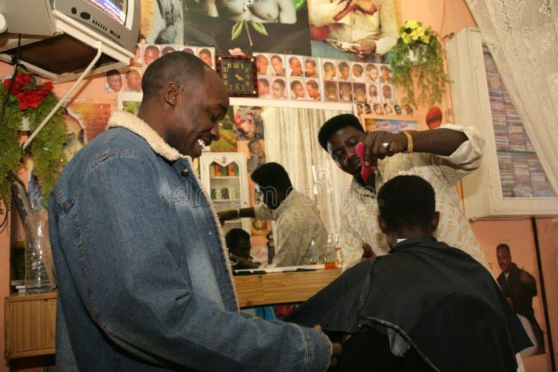 工作在理发店的一个苏丹人难民 库存照片