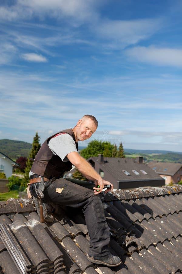 工作在瓦的愉快的盖屋顶的人 库存照片