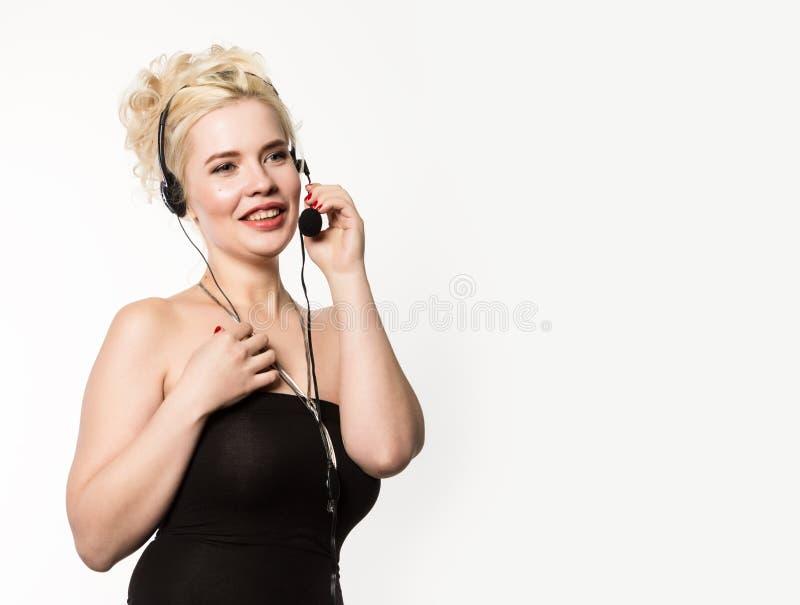 工作在电话中心的性感的微笑的妇女 耳机电话推销妇女谈话在热线服务电话 您的文本的空位 免版税库存图片