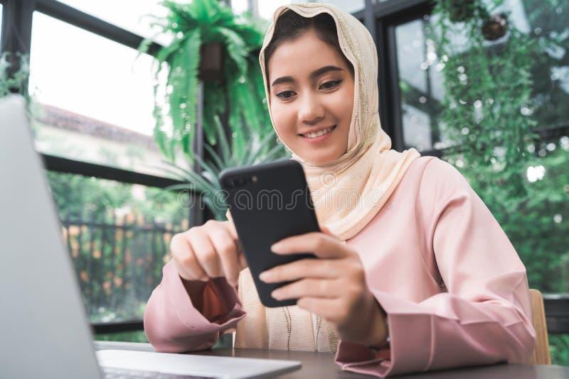 工作在电话的美丽的年轻微笑的亚裔回教妇女在家坐在客厅 库存图片