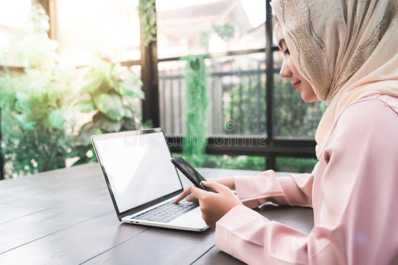 工作在电话的美丽的年轻微笑的亚裔回教妇女在家坐在客厅 免版税库存图片
