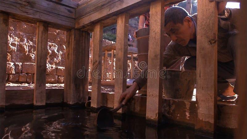 工作在盐领域的中国人 为盐烹饪过程使用盐水 云南 中国 免版税库存照片