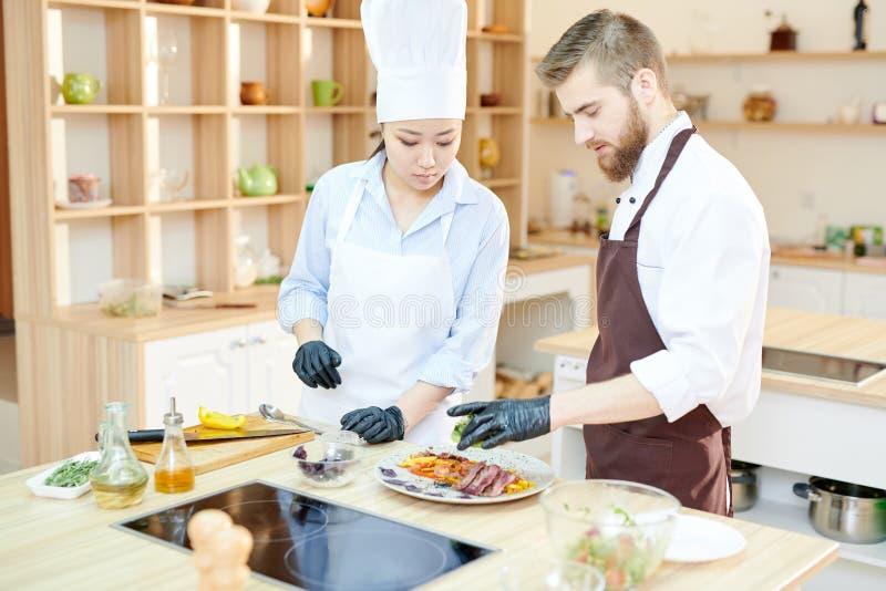 工作在盘的两位厨师 免版税库存图片