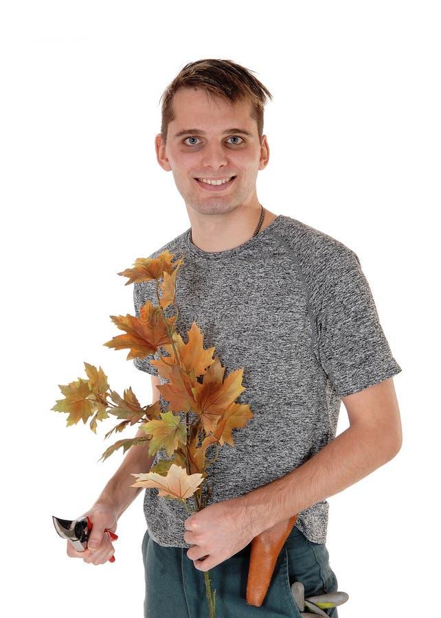 工作在秋天树切开的年轻人 图库摄影