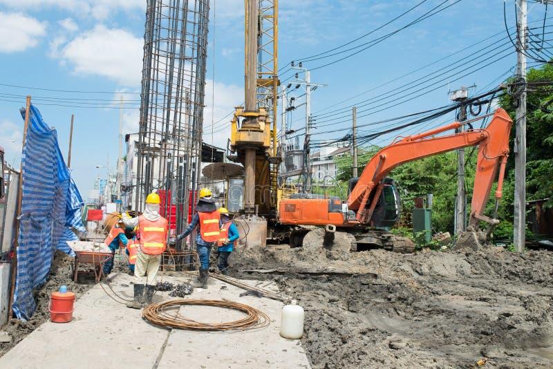 工作在站点桥梁打桩的建筑工人 免版税库存照片