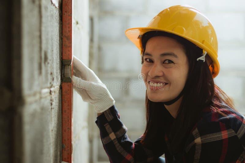 工作在站点的亚洲妇女与愉快一起使用 库存照片