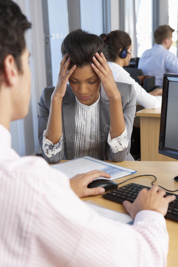工作在繁忙的办公室的被注重的雇员 库存照片