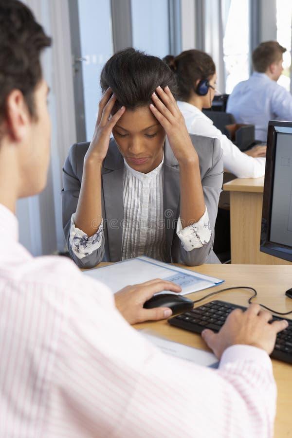 工作在繁忙的办公室的被注重的雇员 免版税库存图片
