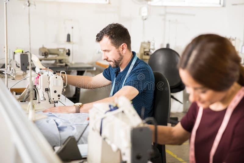 工作在纺织品工厂的人们 免版税图库摄影