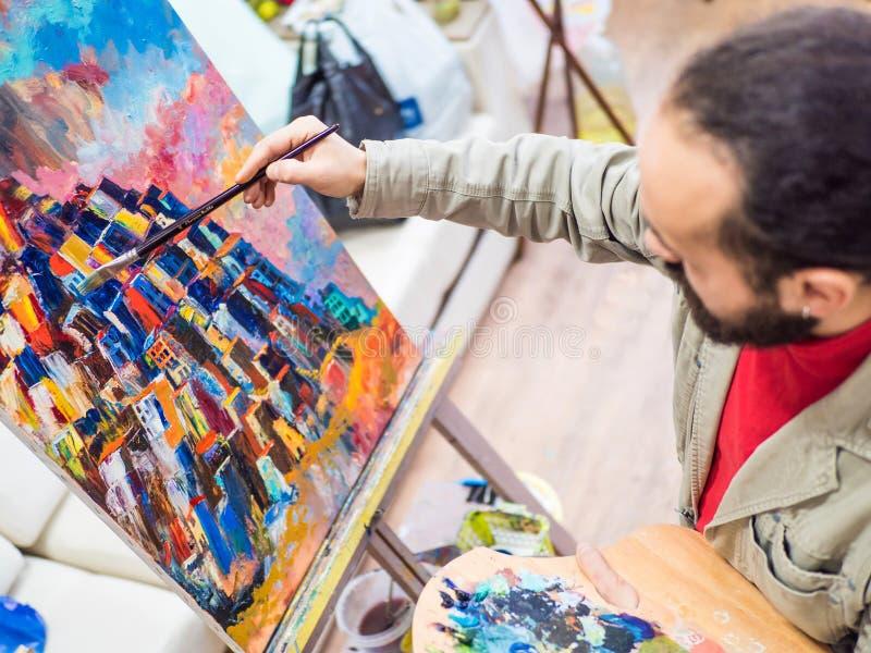 工作在绘画的男性艺术家在明亮的白天演播室 免版税库存照片