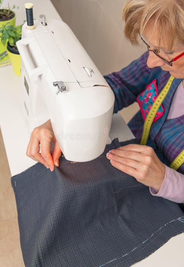 工作在缝纫机的资深裁缝妇女 免版税库存图片