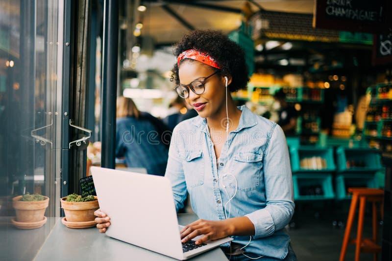 工作在网上在咖啡馆的被聚焦的年轻非洲妇女 库存照片