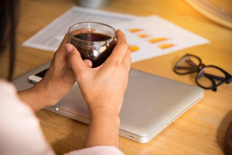 工作在网上观看和浏览膝上型计算机的轻松的女商人坐在桌面在办公室 免版税图库摄影