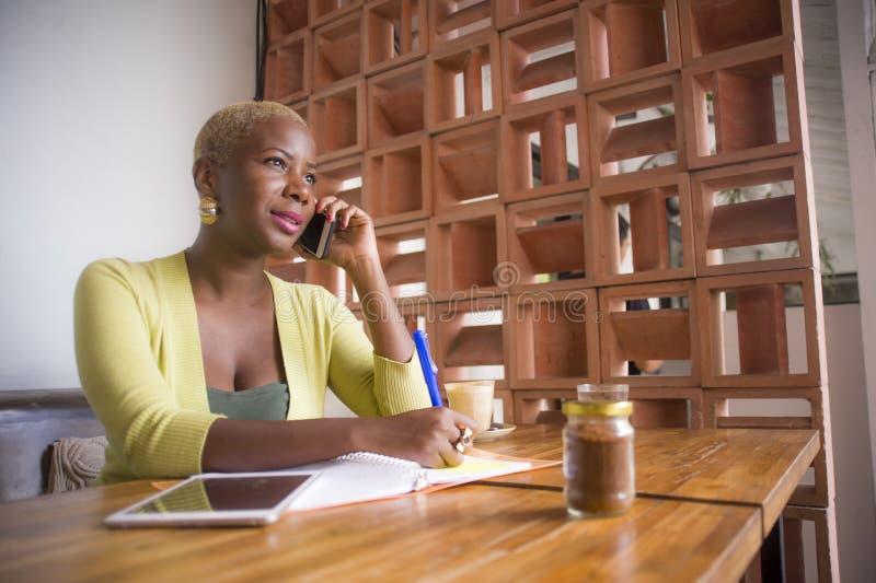 工作在网上谈话在手机的年轻典雅和美丽的黑人非裔美国人的女商人在采取的咖啡店没有 图库摄影
