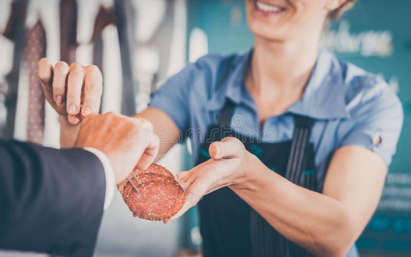 工作在肉店-递肉的售货员对cust 图库摄影