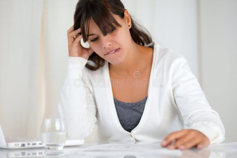 工作在膝上型计算机前面的被注重的少妇 免版税库存照片